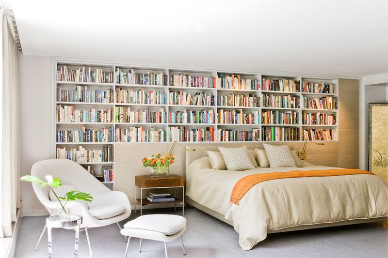 A modern bedroom with a wall of bookshelves behind the bed.