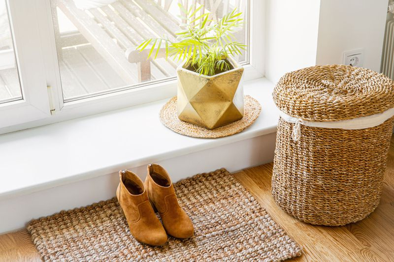 A decorative seagrass hamper next to a window with a plant and a pair of women's shoes.