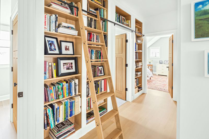 A library in the hallway of a home, equipped with a ladder that allows you to get books from the upper shelves.