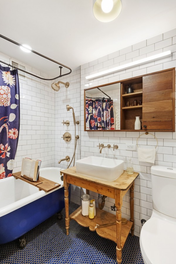 Image of a renovated bathroom with white subway tile and clawfoot tub