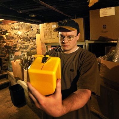 Person inspecting object in basement for radioactivity.
