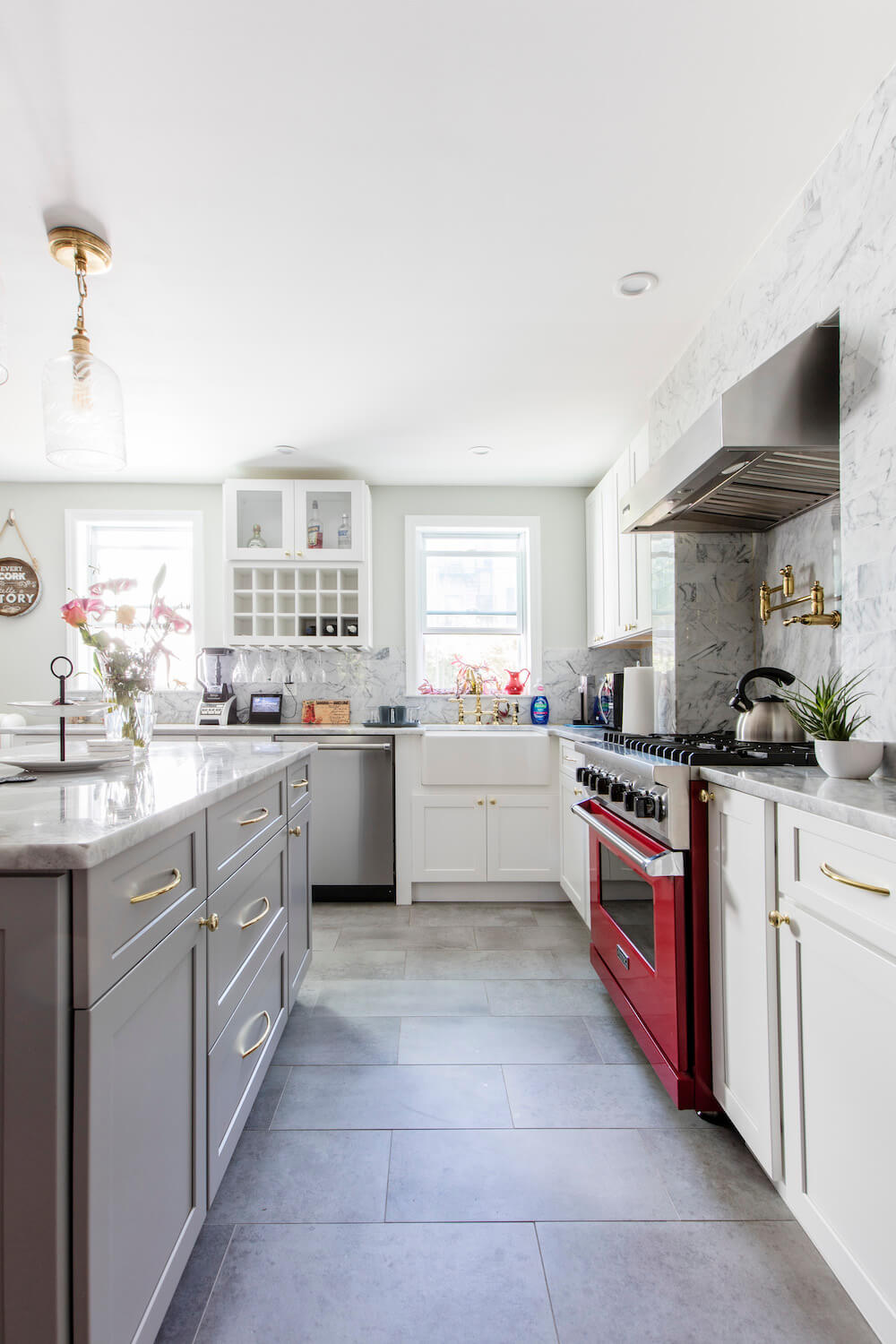 Kitchen with tile floor, gray kitchen island, gold cabinet pulls