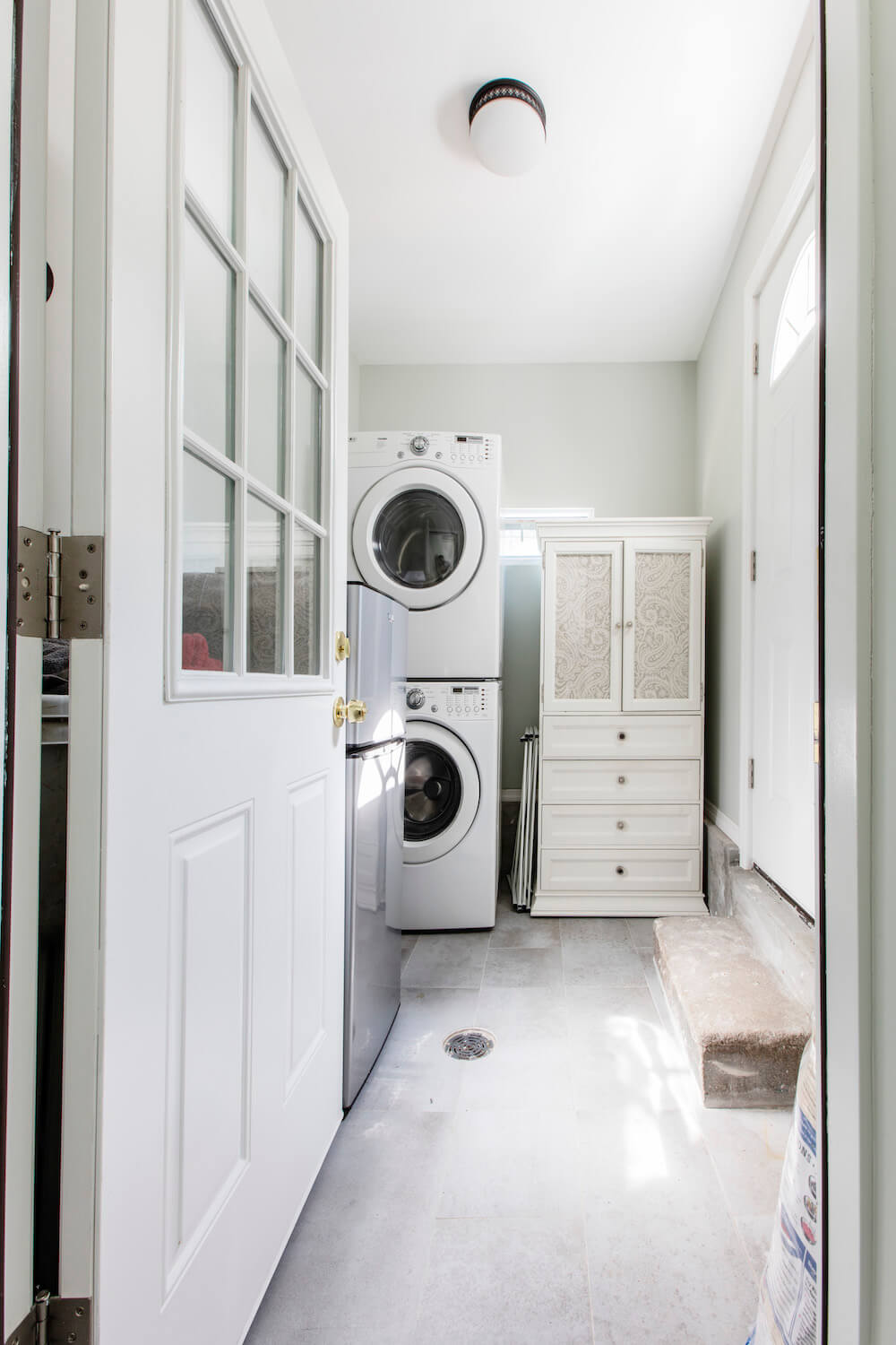 Door opening into laundry room with stacked washer and dryer, with white pantry storage