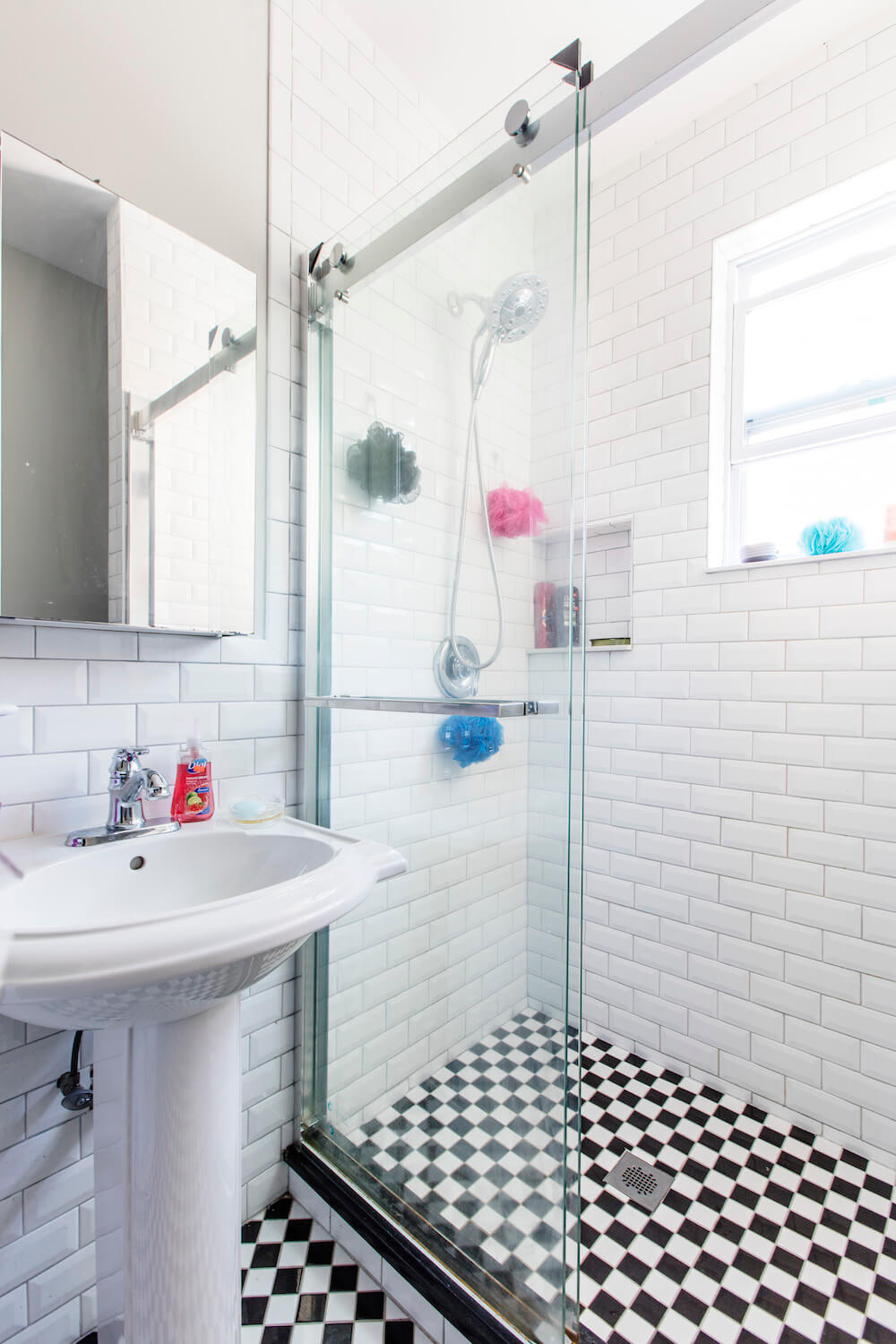 Walk-in shower with black and white checkered floor, glass shower door, and pedestal sink
