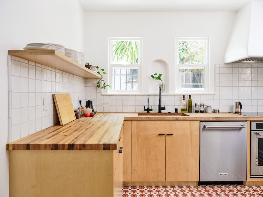 Remodeled kitchen with white tile walls, open shelves and plywood cabinets