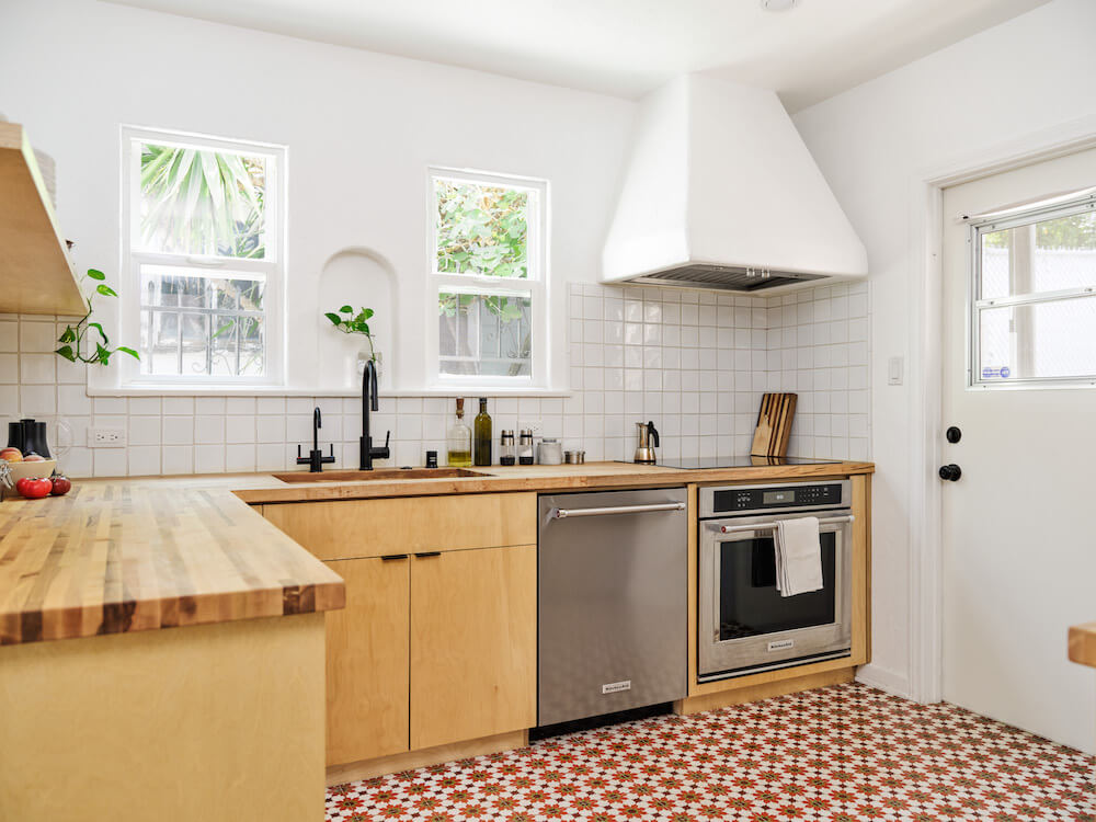 Kitchen with plywood cabinets, Moroccan floor tiles, plastered oven range and white wall tile