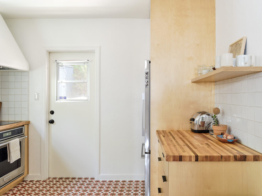 Kitchen with plywood cabinets, Moroccan floor tiles, open shelving and white wall tile