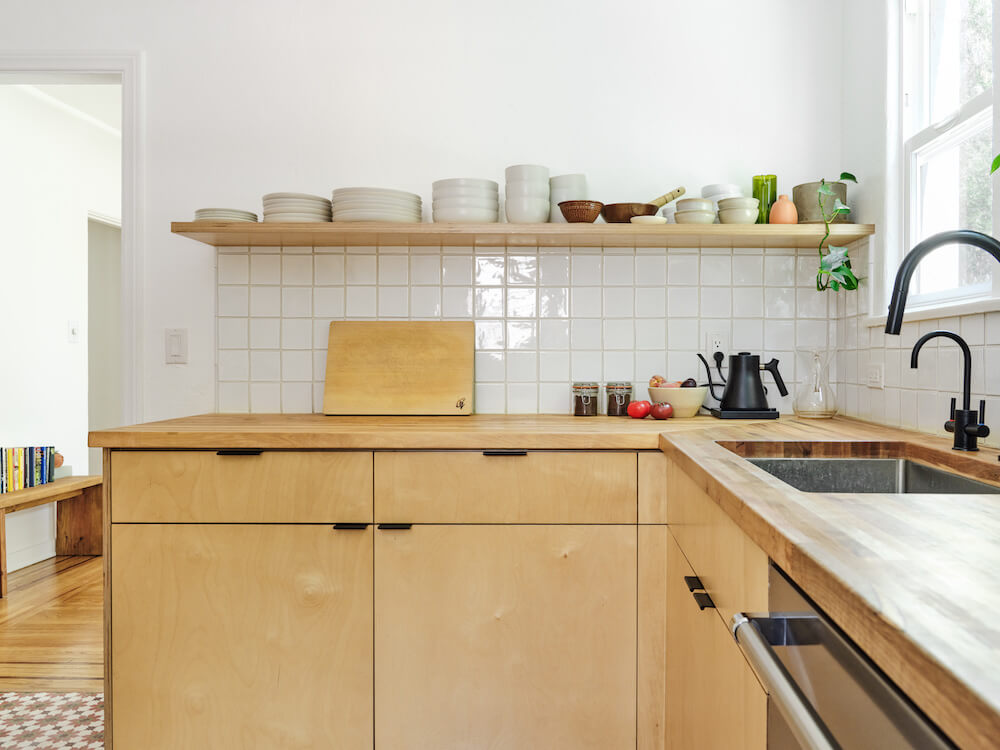 Open shelving holding bowls and plates over plywood kitchen cabinets and clay tile wall