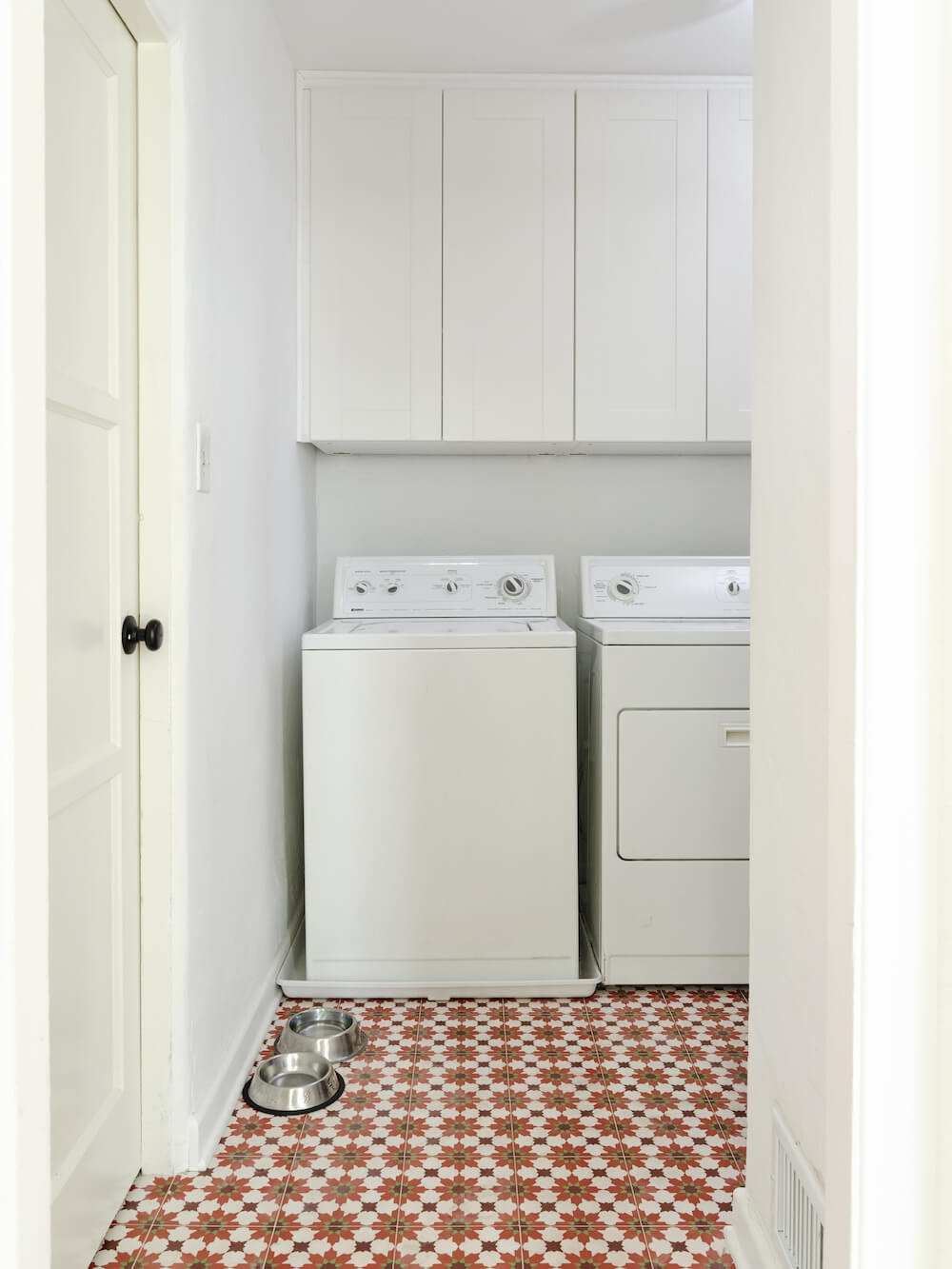 Laundry room with Moroccan floor tiles, white cabinets and white washer and dryer