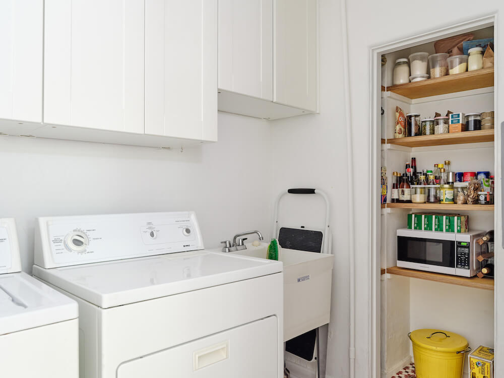 Laundry room with white utility sink, white cabinets and open pantry storage