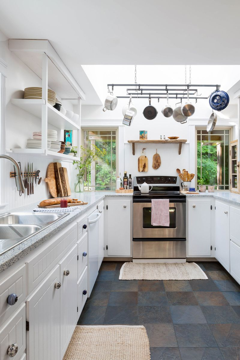 A gallery kitchen with several storage solutions including open shelving, magnetic wall mounts for knives and an overhead pot rack.