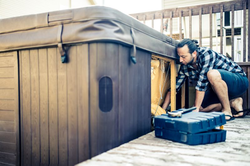 A man crouches to inspect the inner workings of a hot tub.