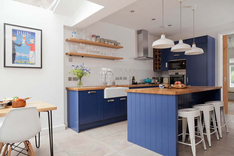 A small kitchen with a blue painted island that allows the space to be more open than a traditional galley kitchen.