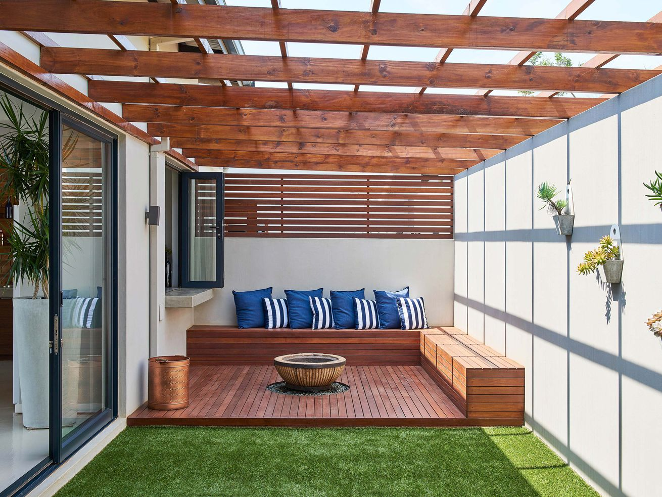 A wooden pergola attached to a house with a fire pit underneath and bench seating.