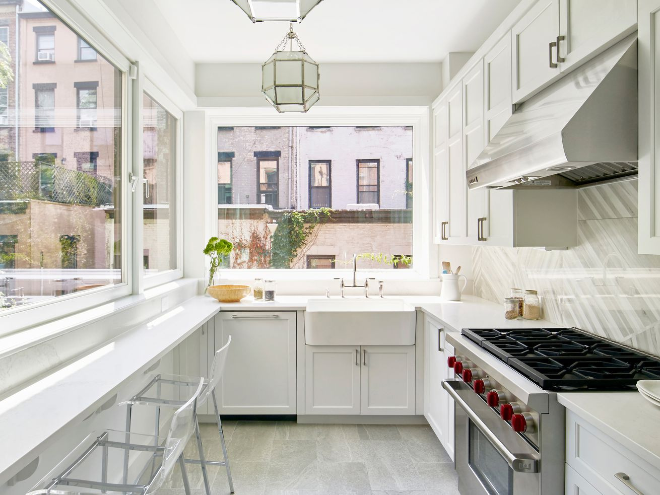 A white galley kitchen with large windows on two sides, as well as pendant lights down the length of the room.