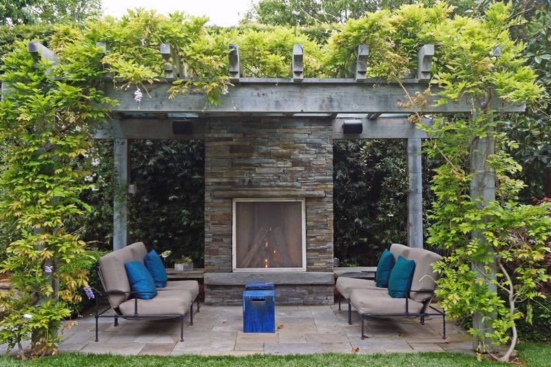 A wooden pergola with vines growing along the sides and top. Under the shaded area is stone fire place and seating.