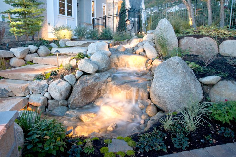 A lit up water feature filled with rocks.