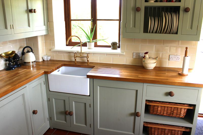 The corner of a kitchen with a small farmhouse sink and a wood countertop.