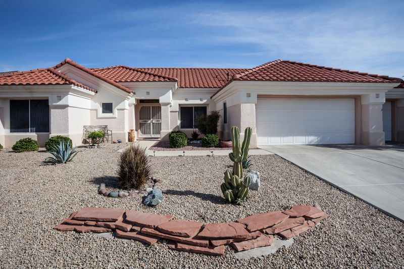 A Southwestern home with a rock front yard, a small slate wall and desert vegetation.