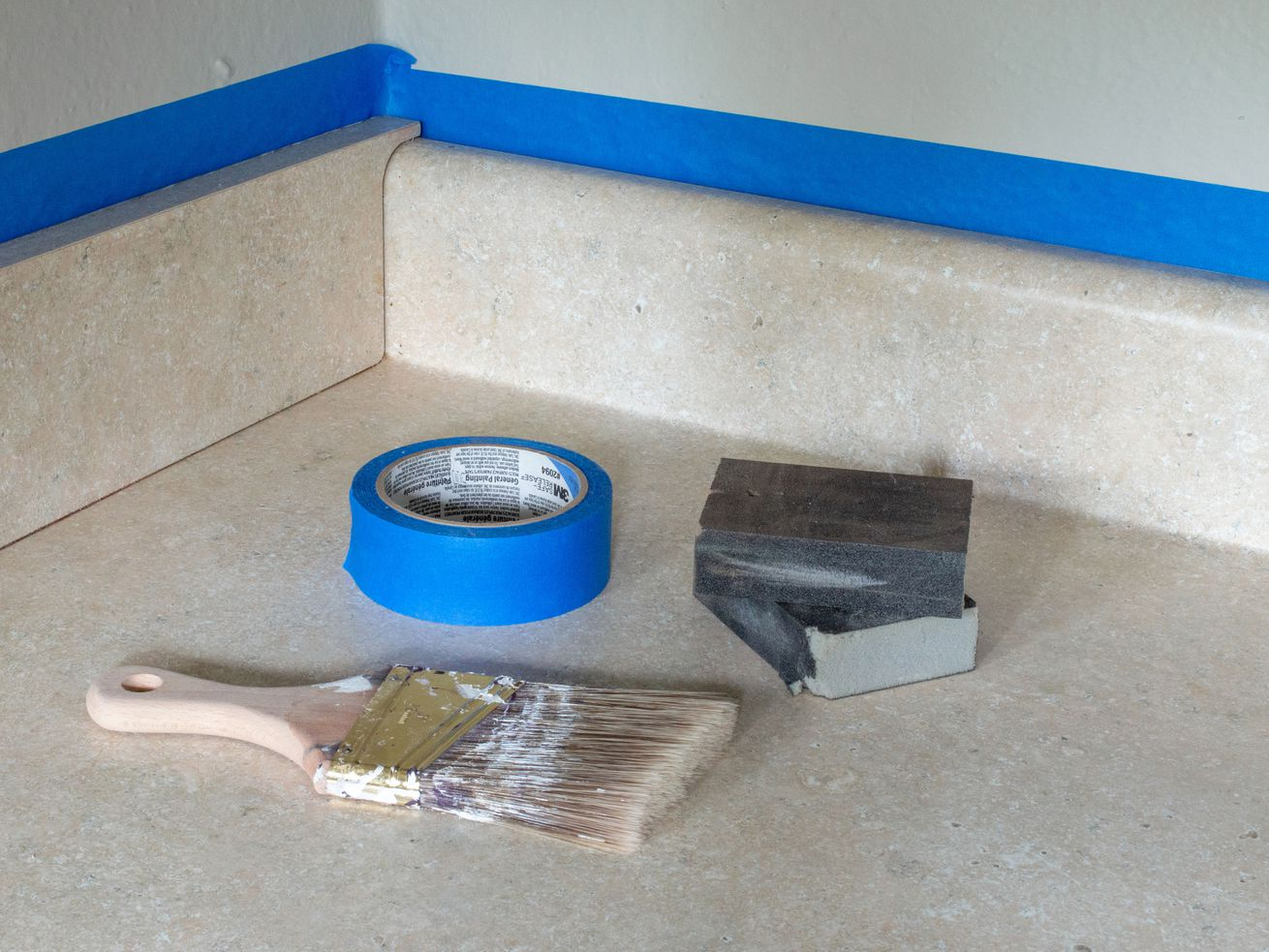 A paintbrush, blue tape, and sanding blocks sit on a beige laminate countertop.