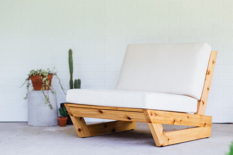 A modern wood lounge chair with white cushions.